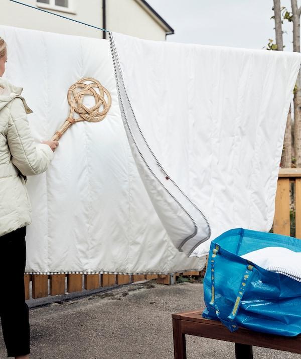 Des couettes suspendues à l'extérieur sur des cordes à linge. Une femme utilise une tapette BORSTAD pour les aérer. Sur un banc à côté, un sac contenant d'autres couettes.