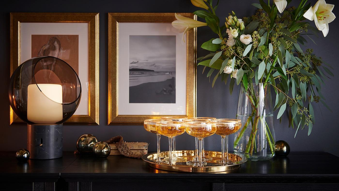 Des coupes à champagne sur un plateau, devant une composition florale dans un vase en verre et deux cadres dorés sur le mur de derrière.