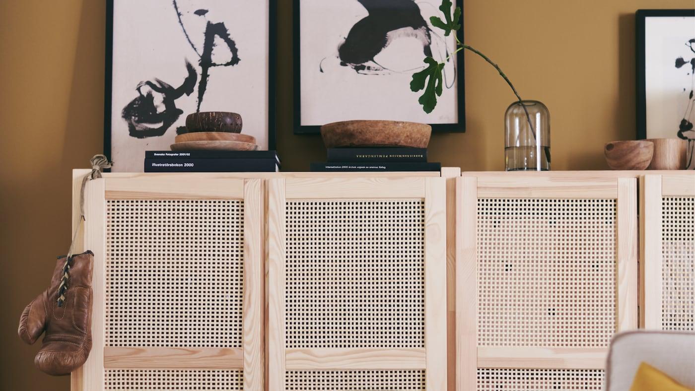 Des étagères IVAR avec des portes en bambou créent un espace pour ranger certaines choses et en exposer d'autres dans un salon à l'ambiance chaleureuse et décontractée.