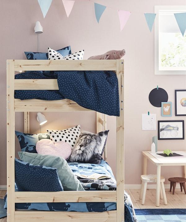 Des lits superposés en bois clair dans une chambre d'enfant avec du linge de lit bleu et des murs roses.