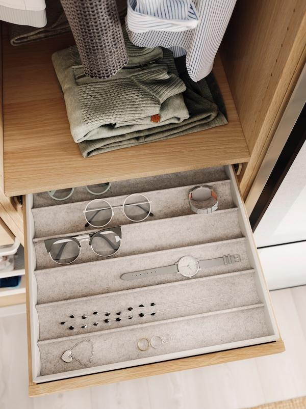 Des lunettes, une montre et des bijoux sont soigneusement disposés dans un rangement pour bijoux KOMPLEMENT glissé dans un des tiroirs peu profonds d'une armoire-penderieouverte.