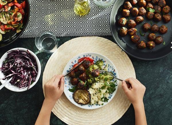 Des mains tenant un couteau et une fourchette au-dessus d'une assiette garnie sur une table avec des plats de légumes et de boulettes végétariennes.