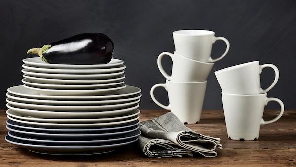 Des mugs DINERA en beige/blanc sont empilés sur un plan de travail aux côtés d'une pile d'assiettes de différentes tailles en beige et gris/bleu.