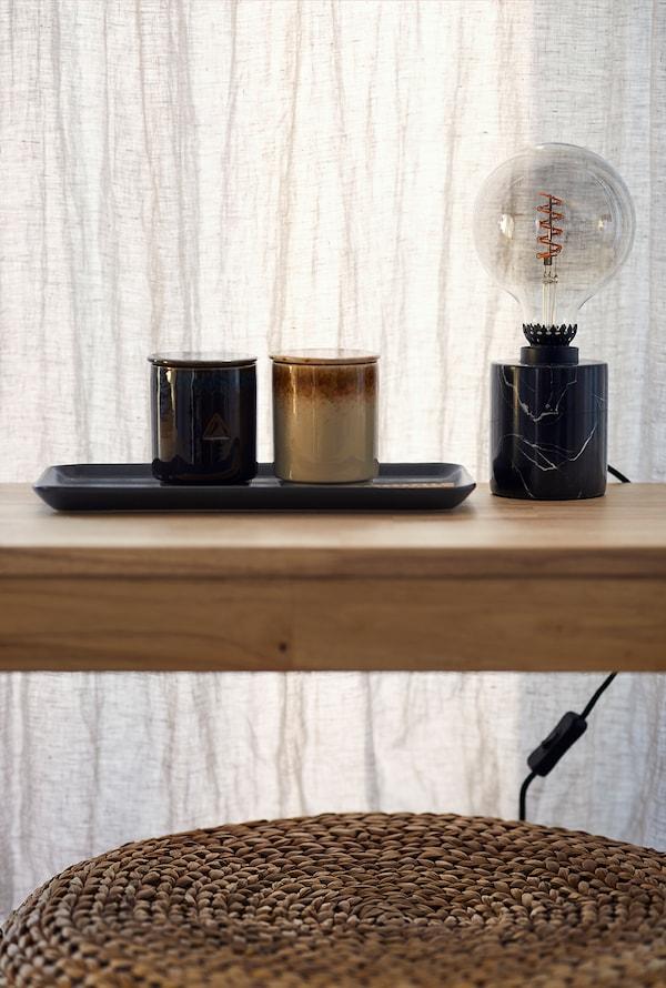 Des objets de décoration et une lampe posés sur un banc en bois massif.