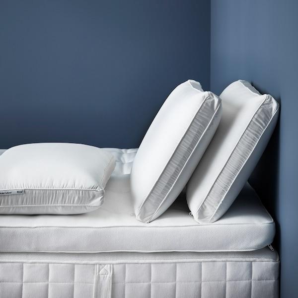 Des oreillers blancs et une alèse sur un matelas blanc.