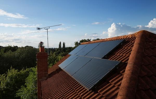 Des panneaux solaires montés sur le toit d'une demeure résidentielle.
