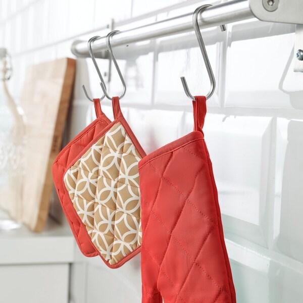 Des poignées isolantes et un gant isolant à motifs rouge et or suspendus à une barre argentée dans une cuisine.