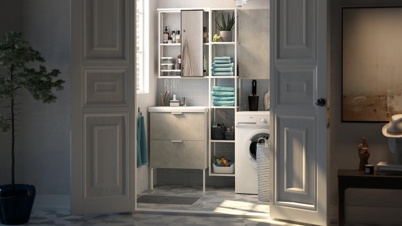 Des portes blanches ouvertes sur une petite salle de bain avec des étagères blanches installées entre un lavabo blanc et un lave-linge.