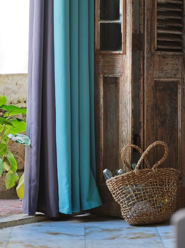 Des rideaux occultants en mauve et turquoise suspendus à une porte en bois ouverte, à côté de laquelle est placé un panier tissé.