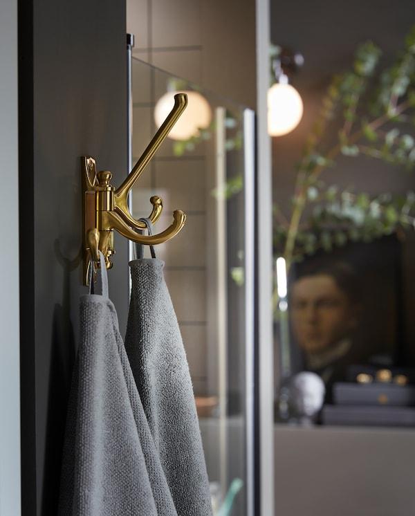 Des serviettes grises sèchent, suspendues au crochet mobile triple KÄMPIG, en couleur laiton, fixé au mur à côté d'une douche.