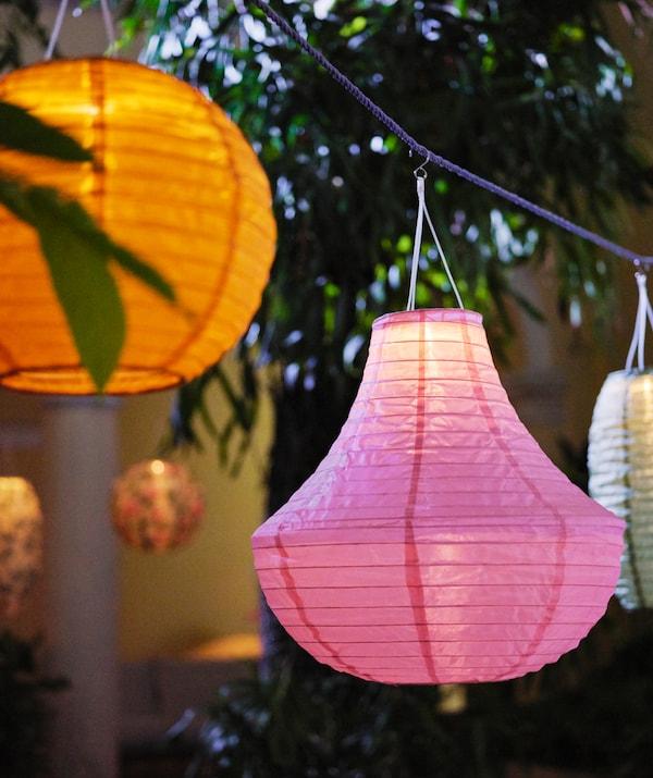 Des suspensions à énergie solaire SOLVINDEN de différentes formes et couleurs accrochées à un câble dans un jardin.