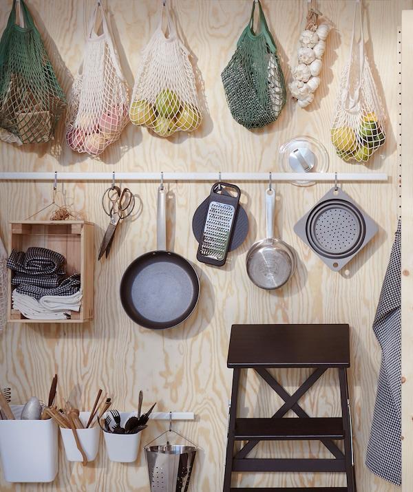 Des ustensiles de cuisine et des sacs pour aliments sont suspendus à des rails blancs SUNNERSTA fixés à un mur en contreplaqué à côté d'un marchepied BECKVÄM noir.
