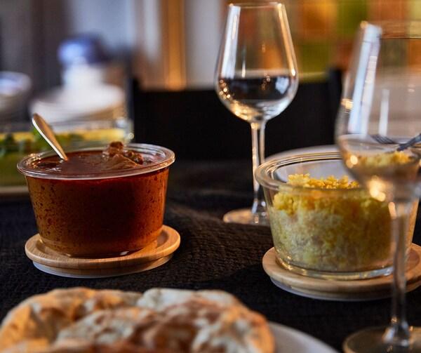 Des verres à vin et des contenants de verre IKEA 365+ à couvercles de bambou remplis de divers aliments.