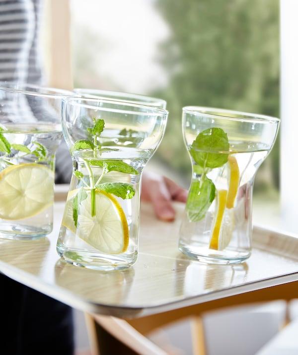 Des verres OMTÄNKSAM faciles à attraper remplis d'eau, de rondelles de citron et de pousses vertes, sur un plateau antidérapant.