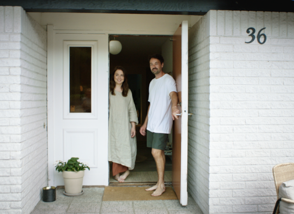 Designer Mikael Axelsson and woman opening the door to a house.
