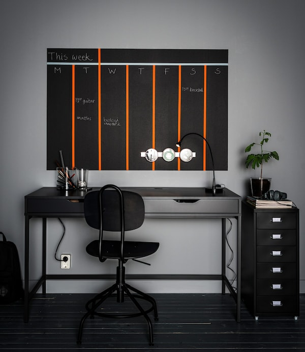 Desk organisation with drawer inserts, magnetic containers and a painted wall calendar above a grey desk with two drawers.