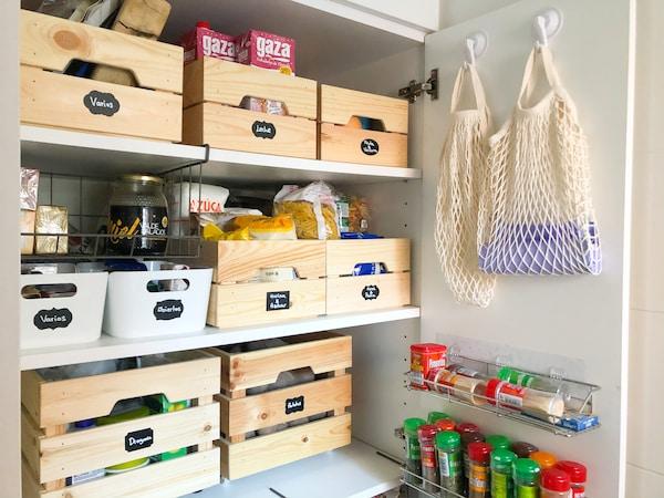 Despensa ordenada con cajas de madera con etiquetas