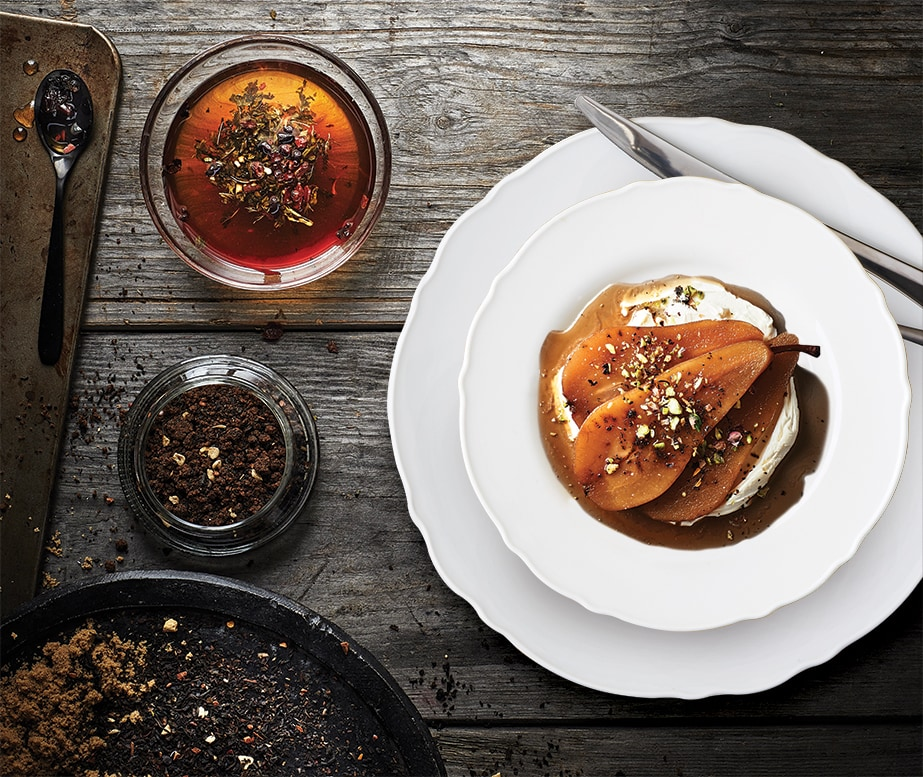 Dessert aux poires servi dans une assiette blanche posée sur une table en bois d'allure rustique.