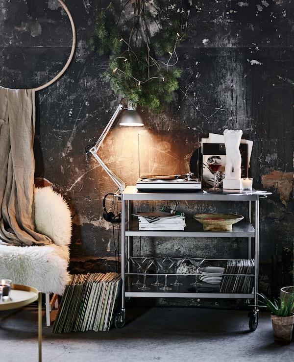 Desserte utilisée comme étagère et portant table tournante, lampe de travail et des verres à martini.