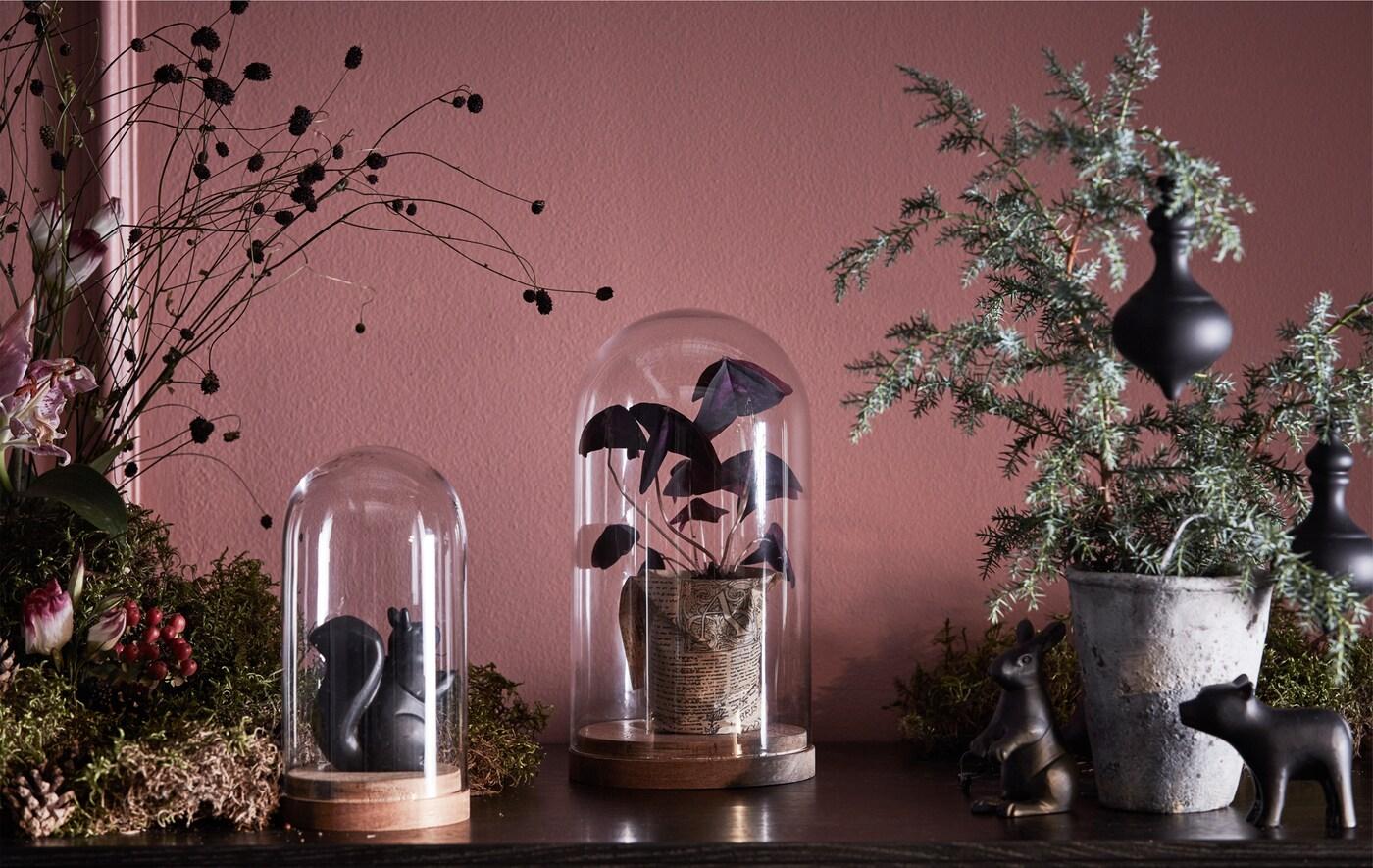 Dessus d'une vitrine décoré de verdure, de fleurs et de cloches en verre.