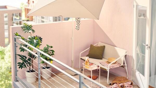 Det er en solrig eftermiddag på denne altan i storbyen med hvide havemøbler, f.eks. en 2-pers. sofa og en parasol.