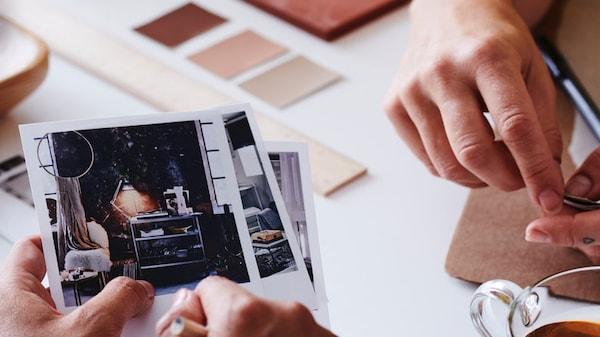 Détail de deux mains montrant une pile de photographies de meubles, avec des catalogues et des échantillons de peinture sur le plateau de la table derrière eux.