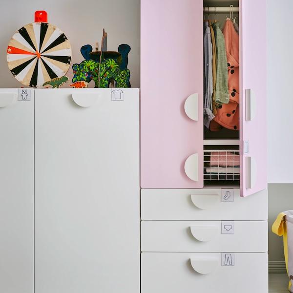 Detail dětského pokoje a skříně s bílými a růžovými dvířky.