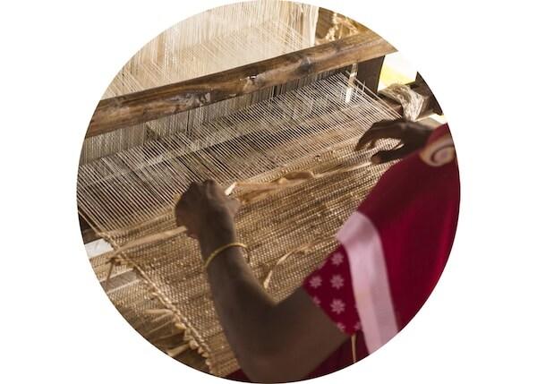 Detail einer Frau, die an einem Webstuhl einen Teppich webt.