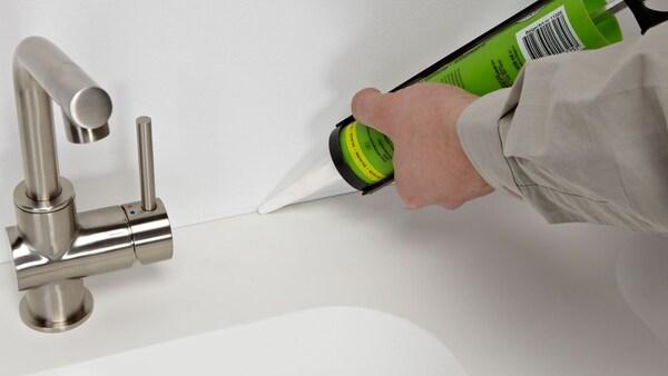 Detail koupelny s baterií a vanou, v rohu ruka instalatéra, který aplikuje silikon na okraje vany