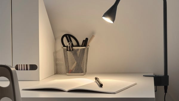 Detail na stolnú lampičku svietiacu na otvorený zošit s ceruzkou.