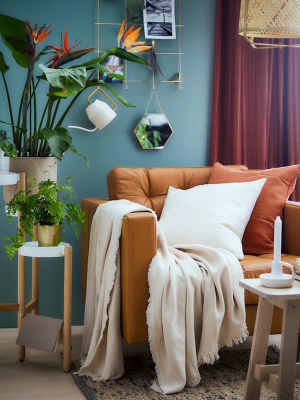 Detail obývacího pokoje s oranžovo-hnědou pohovkou, bílým plédem a polštářem, stojanem na květiny a velkými pokojovými květinami.