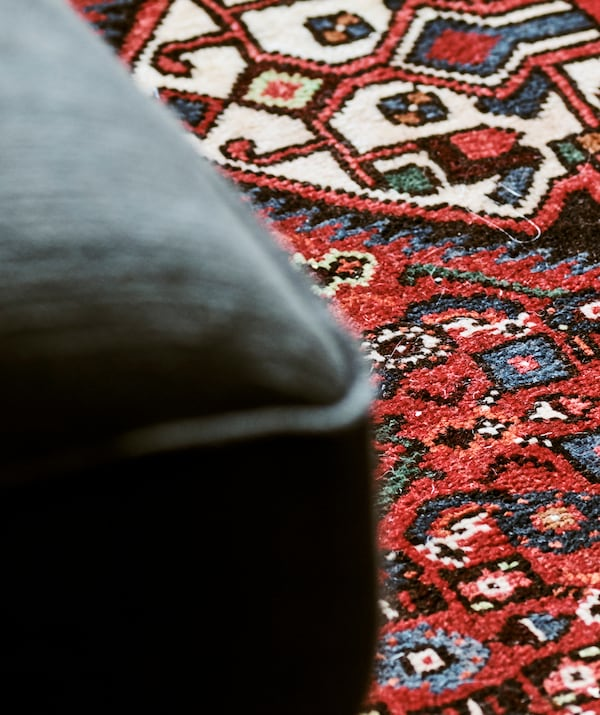 Detail of a Persian rug woven into a pattern with blue and green shapes on a red background.