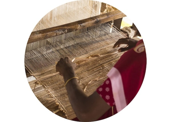 Detail of a woman weaving a rug on a loom.