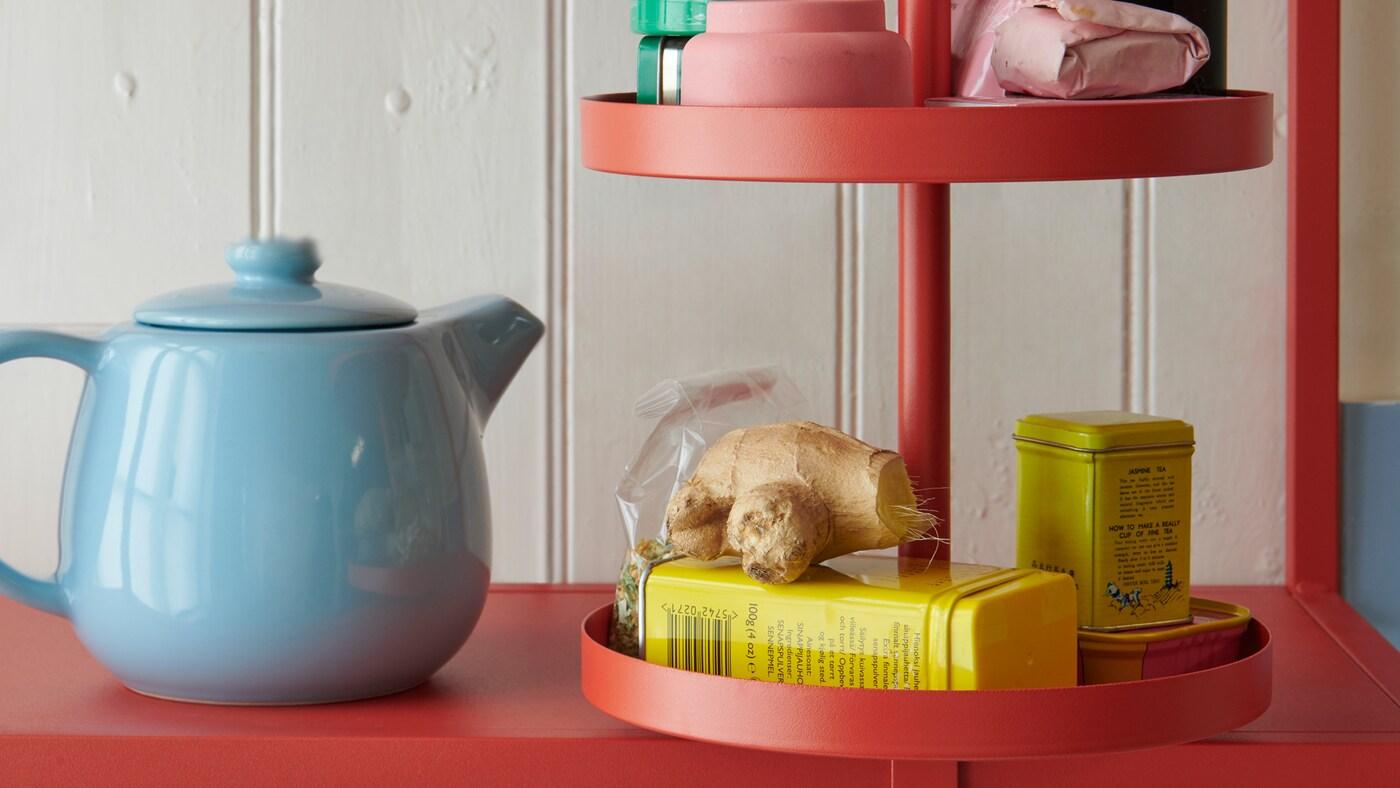 Detail otočné police ENHET v červenooranžové barvě, na polici je různé kuchyňské náčiní a potraviny
