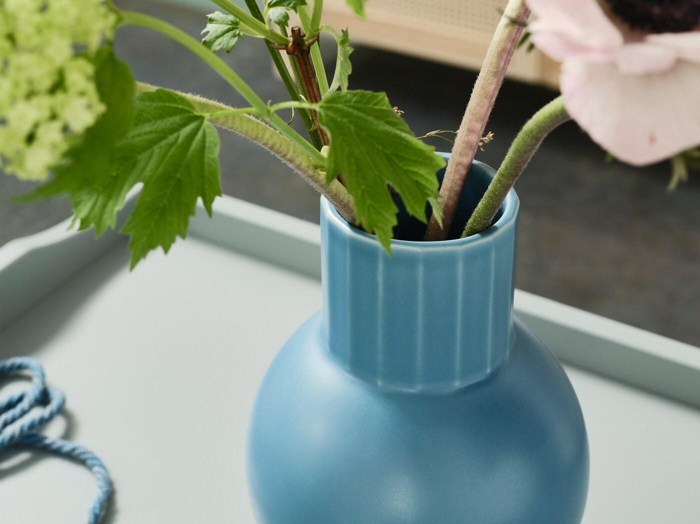 Detail vázy OMFÅNG v modré barvě na okdládacím stolku, ve váze jsou zelené rostliny