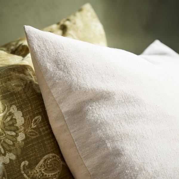 Detalhe de duas capas de almofada em branco e verde.