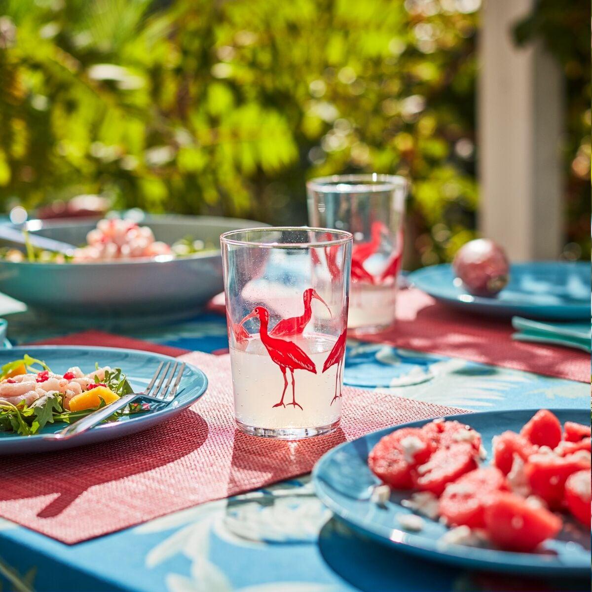 Detalhe de um copo com desenhos de flamingos e pratos azuis