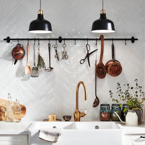 Detaljbild av köksbänken, porslinsvask och mässingskran.
