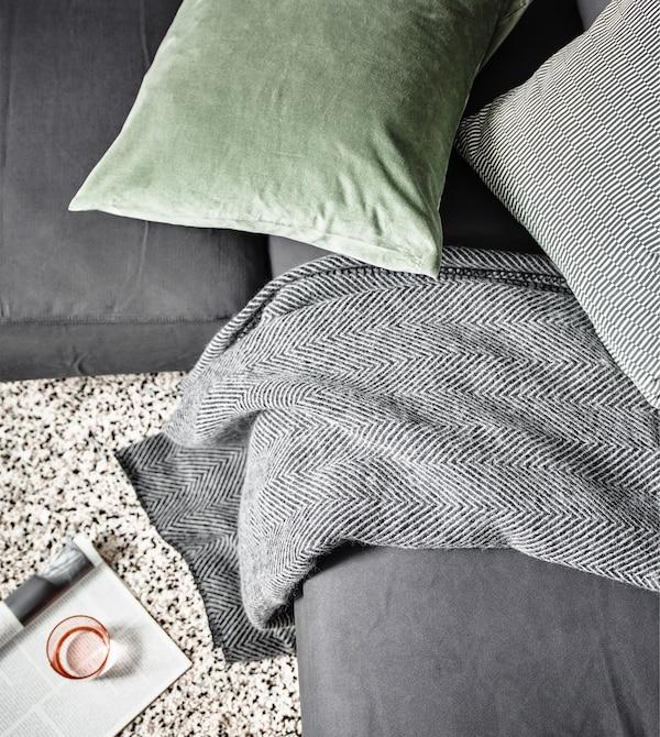 Detall d'una manta IKEA STRIMLÖNN amb estampat d'espiga sobre un sofà gris amb un coixí verd.