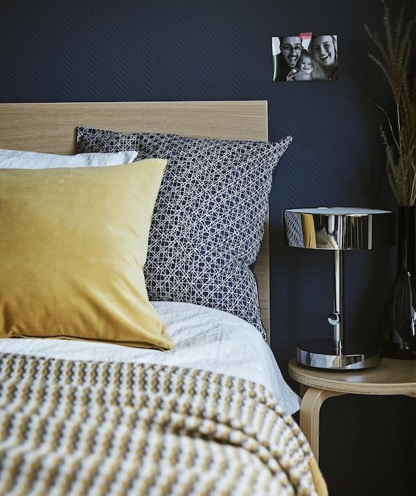 Detalle de la esquina de una cama, mesilla de noche y lámpara junto a una pared azul oscuro.