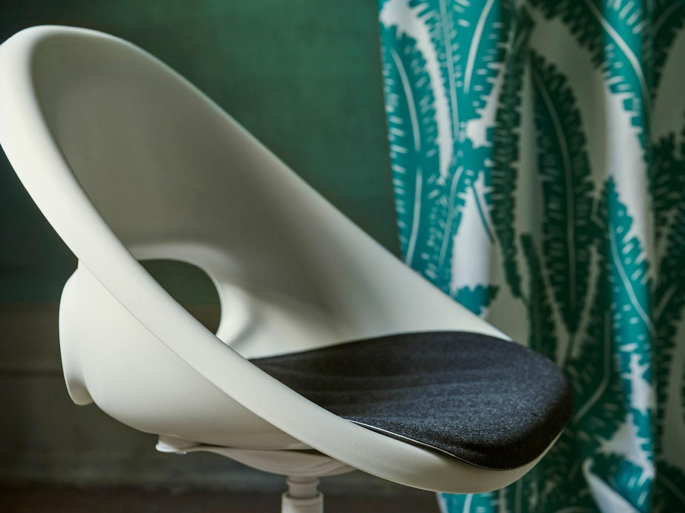 Detalle de la silla giratoria LOBERGET/BLYSKÄR blanca con un diseño retro redondeado en una habitación verde.