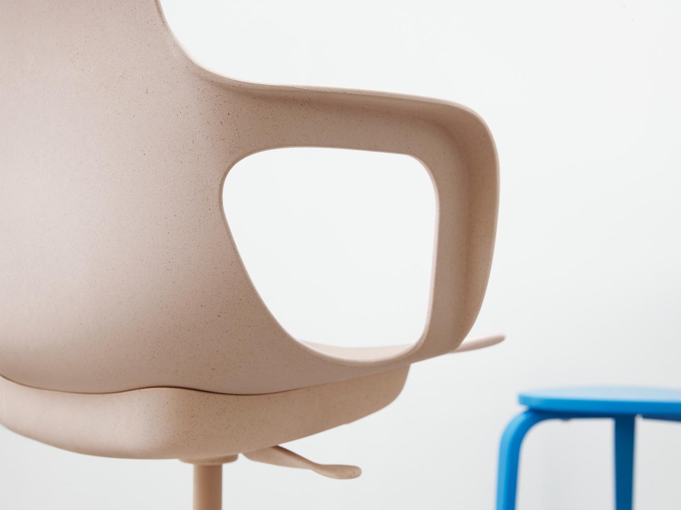 Detalle de la silla giratoria ODGER con su asiento cóncavo, respaldo redondeado y reposabrazos en blanco/beige o negro.