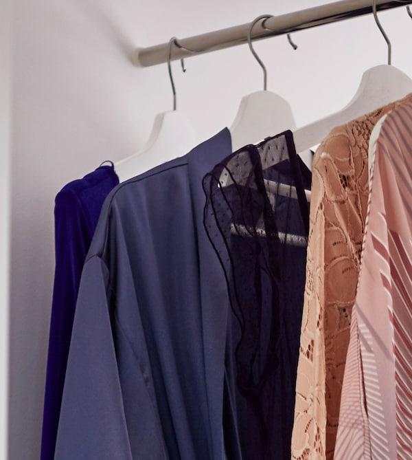 Detalle de ropa colgada en una barra para ropa en un armario blanco.