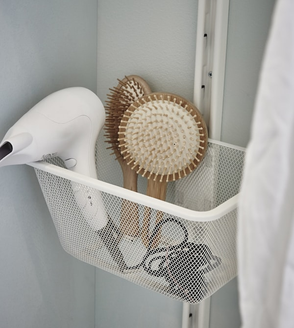 Detalle de un secador de pelo y diferentes cepillos almacenados en la cesta de rejilla blanca ALGOT.