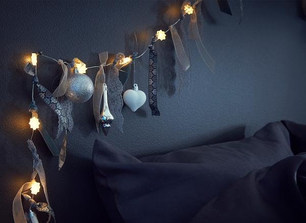 Detalle de una guirnalda luminosa decorada con cintas, tiras de tela y adornos sobre una cama.