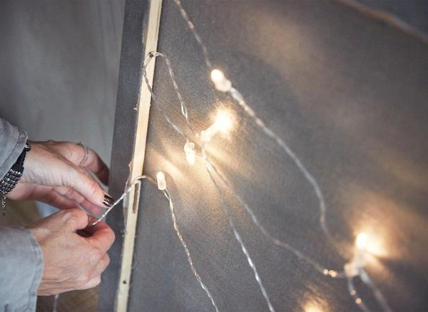 Detalle de una guirnalda luminosa enganchándose a la parte posterior del marco de un lienzo.