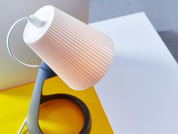 Detalle de una lámpara de trabajo SVALLET, mostrando la pantalla dirigida blanca y la base en color gris oscuro.