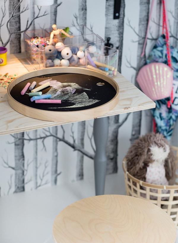 Detalle de una pequeña estantería de madera con juguetes y tiza en una bandeja con superficie de pizarra para escribir en ella.
