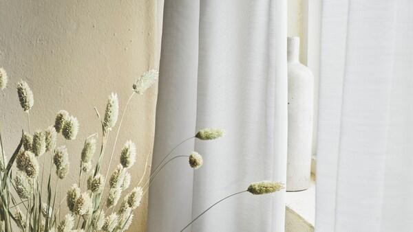 Detalle de una ventana con una cortina purificadora de aire GUNRID y un jarrón. Cerca, en el suelo, hay unas ramitas ornamentales.