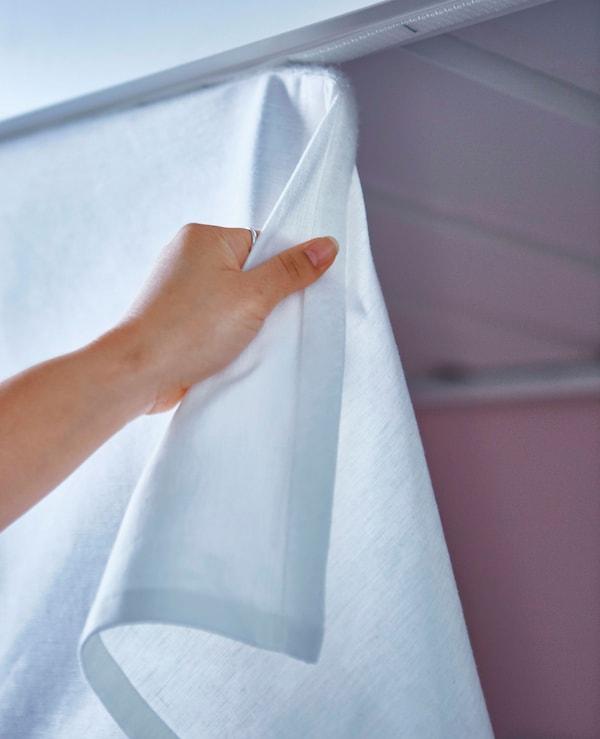 Detalle dunha man retirando unha cortina suxeita con velcro.